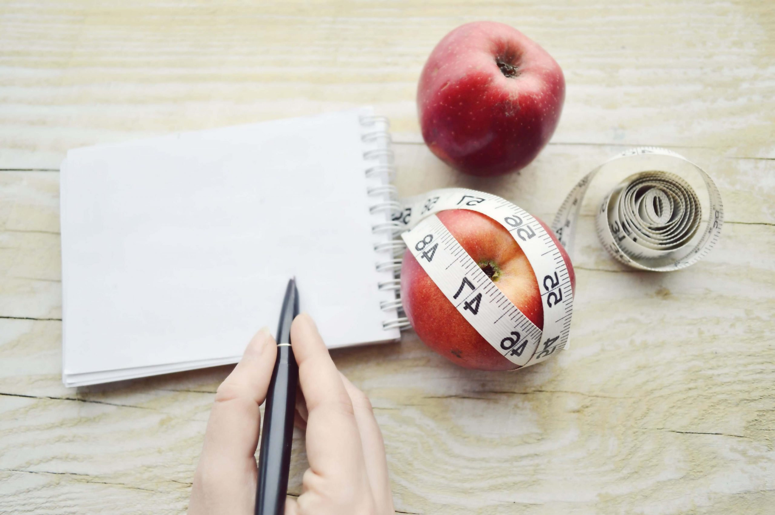 writing health plan with two apples and measuring tape